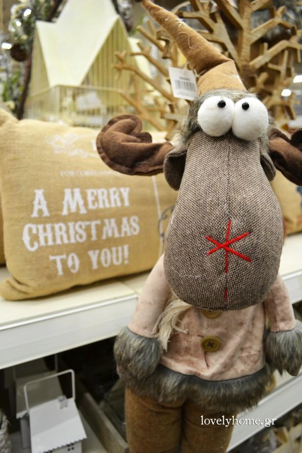 Γλυκούλης τάρανδος για να διακοσμήσεις το καθιστικό σου και στο βάθος μαξιλάρι διακοσμητικό merry christmas