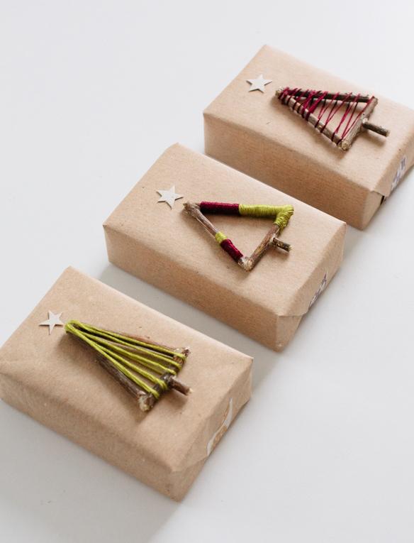 Τυλίγοντας τα πακέτα των δώρων με απλό craft χαρτί περιτυλίγματος, έχετε στη συνέχεια την δυνατότητα να δημιουργήσετε την πιο diy διακόσμηση, όπως αυτά τα χριστουγεννιάτικα δεντράκια από ξυλάκια, χαρτί και νήμα
