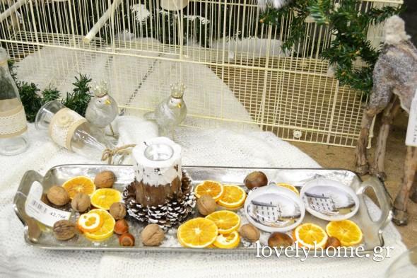 Μακρόστενος μεταλλικός δίσκος διακοσμημένος με στολίδια διάφανα, αποξηραμένους καρπούς και φέτες πορτοκαλιού κι ένα κηροπήγιο, ξύλινο