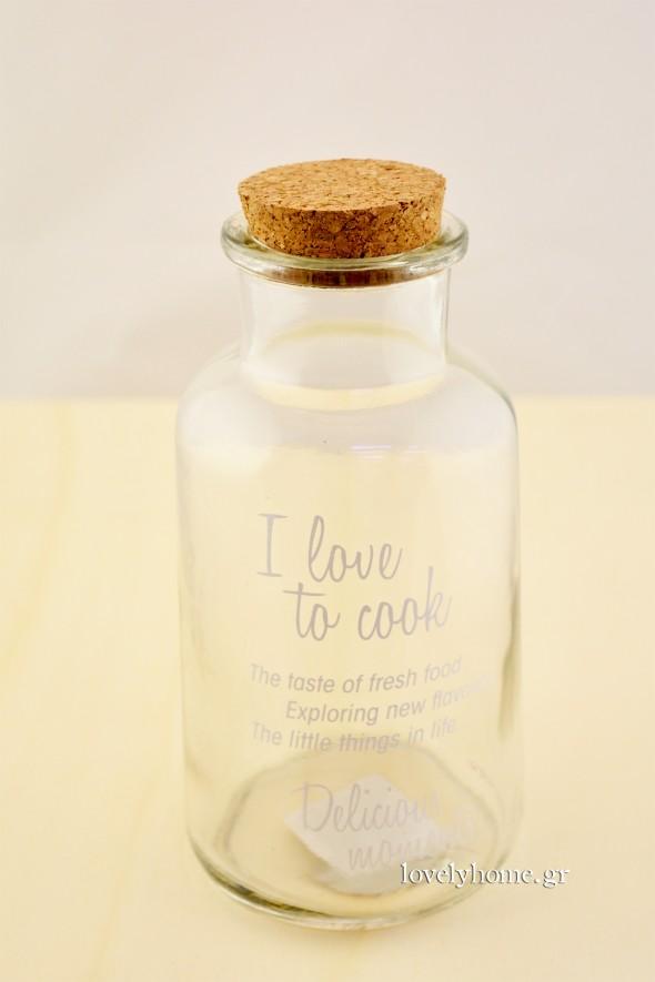 Στο γυάλινο διαφανές μπουκάλι με τον φελλό, υπάρχει εκτυπωμένη φράση I love to cook